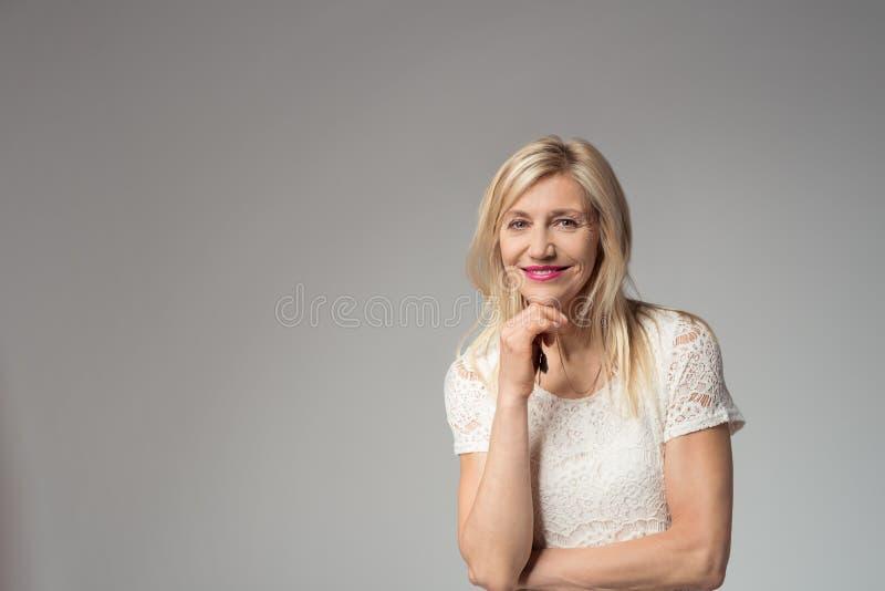 Zekere Glimlachende Vrouw op Grijs met Exemplaarruimte stock afbeeldingen