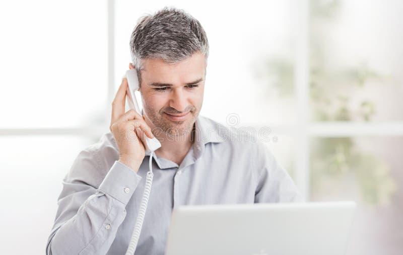 Zekere glimlachende zakenman en adviseur die in zijn bureau werken, heeft hij een telefoongesprek: communicatie en bedrijfs conce stock foto's