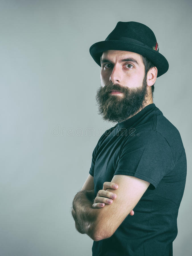 Zekere hipster zwarte hoed dragen en t-shirt die camera met gekruiste wapens bekijken stock afbeelding