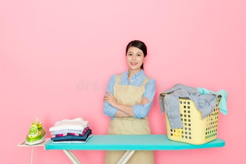 Zekere huisvrouw die zich op roze achtergrond bevinden stock afbeelding