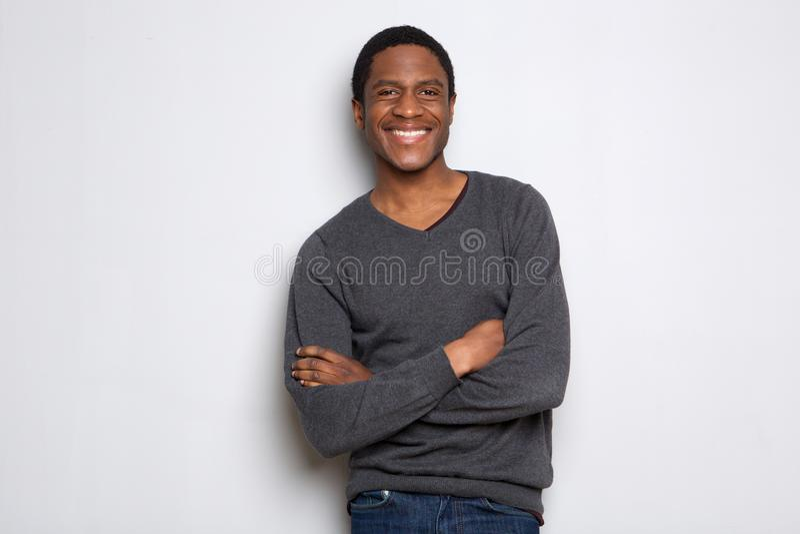 Zekere jonge Afrikaanse Amerikaanse mens die die met wapens glimlachen tegen witte achtergrond worden gekruist royalty-vrije stock foto