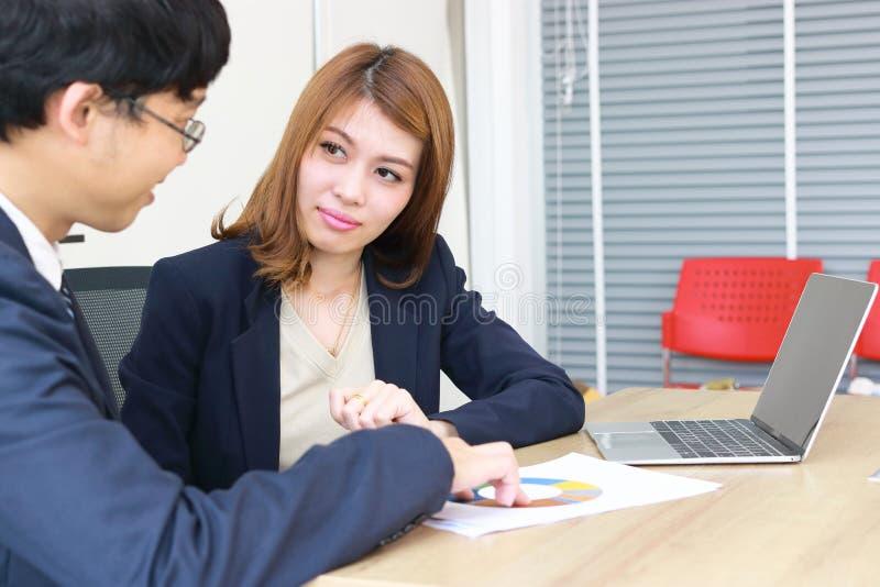 Zekere jonge Aziatische beleggingsadviseur bedrijfsvrouw die aan haar cli?nt bespreken royalty-vrije stock foto