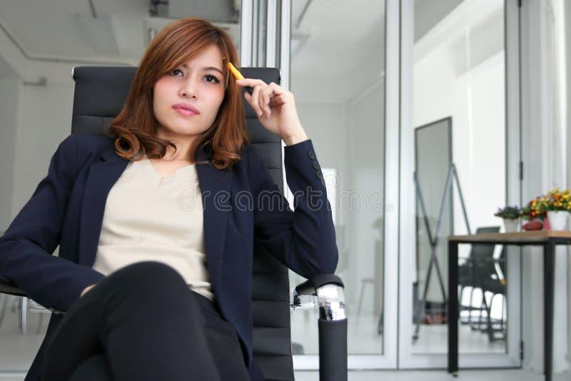 Zekere jonge Aziatische uitvoerende vrouwenzitting en het hebben van idee in werkplaats van bureau stock foto's