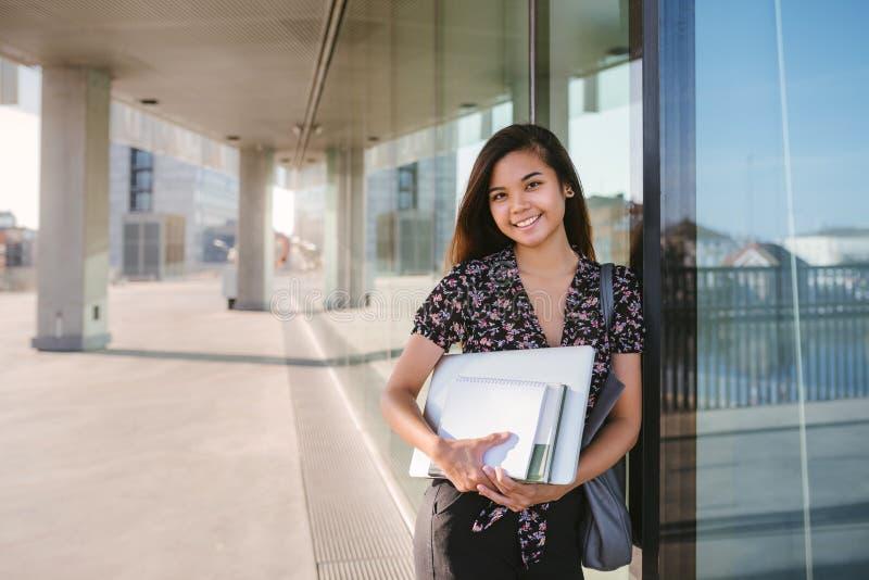 Zekere jonge Aziatische universitaire student die terwijl status op campus glimlachen royalty-vrije stock foto's