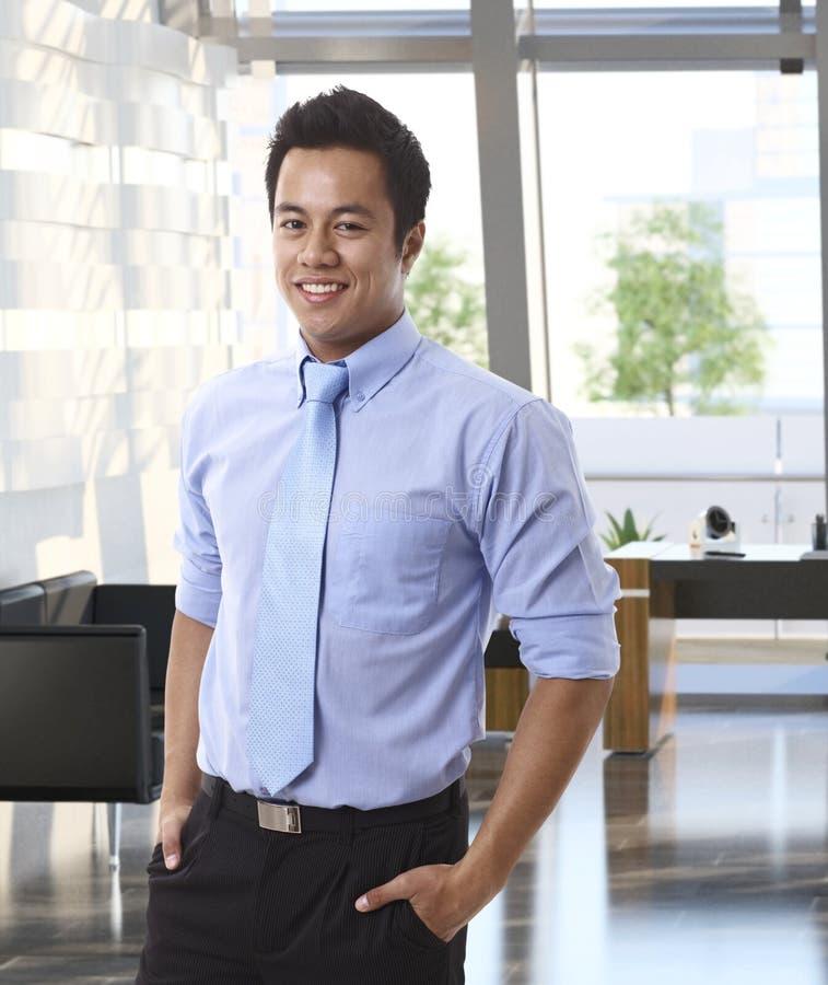 Zekere jonge Aziatische zakenman op kantoor royalty-vrije stock afbeeldingen