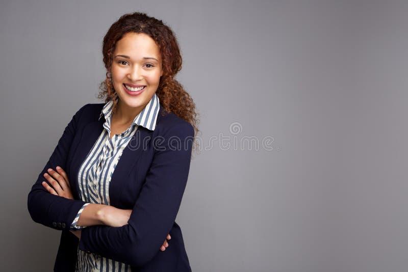 Zekere jonge bedrijfsvrouw die vernederend grijze achtergrond glimlachen royalty-vrije stock fotografie