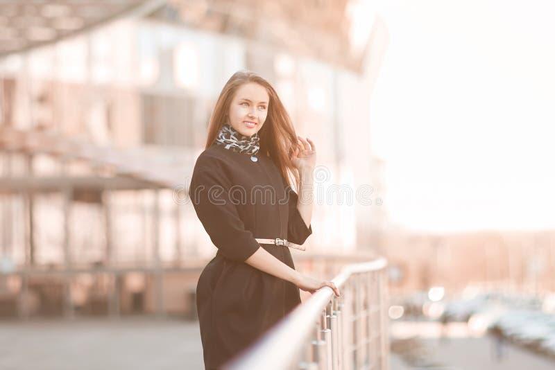 Zekere jonge bedrijfsvrouw die zich dichtbij de moderne bureaubouw bevinden stock fotografie