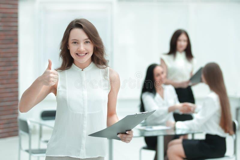 Zekere jonge bedrijfsvrouw met klembord op de achtergrond van commercieel team stock afbeelding