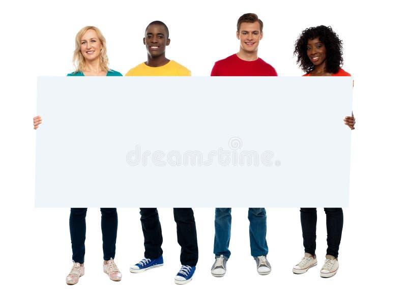 Zekere jonge groep die lege affiche toont stock afbeeldingen