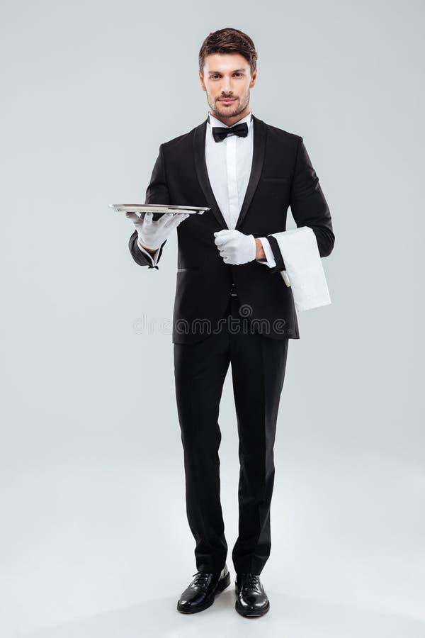 Zekere jonge kelner in smoking die en dienblad bevinden zich houden stock foto