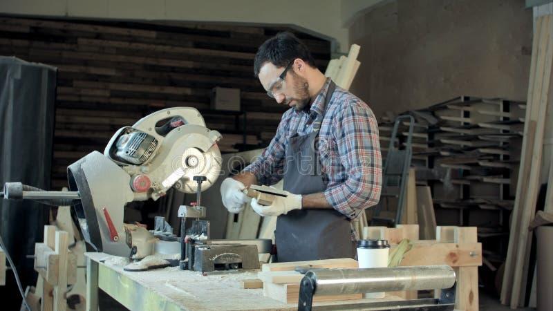 Zekere jonge mannelijke timmerman die met hout in zijn workshop werken royalty-vrije stock afbeelding