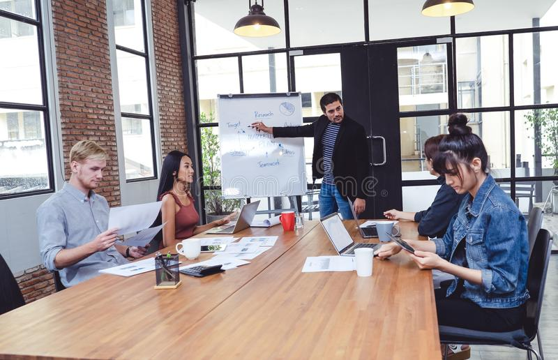 Zekere jonge mens die creatieve presentatie geven aan zijn collega's aan medewerkers in conferentieruimte , Groepswerkconcept Het royalty-vrije stock foto's