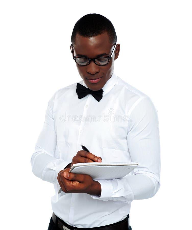 Zekere jonge mens die op blocnote schrijft stock fotografie