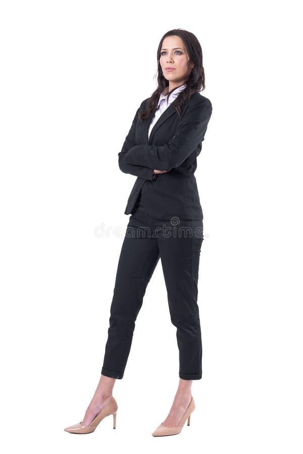 Zekere jonge mooie bedrijfsvrouw die in zwart kostuum omhoog met gekruiste handen kijken stock afbeeldingen