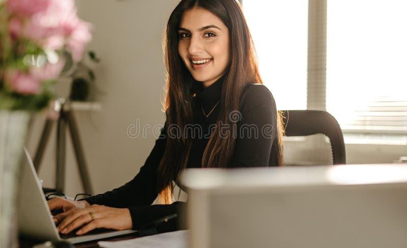 Zekere jonge onderneemster bij haar bureau royalty-vrije stock foto