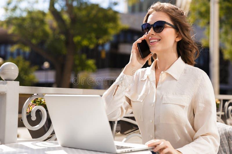 Zekere jonge onderneemster die mobiele telefoon met behulp van stock afbeelding