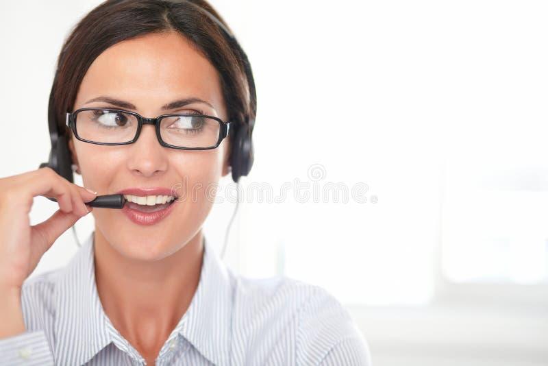 Zekere jonge secretaresse die op hoofdtelefoons spreken royalty-vrije stock afbeelding