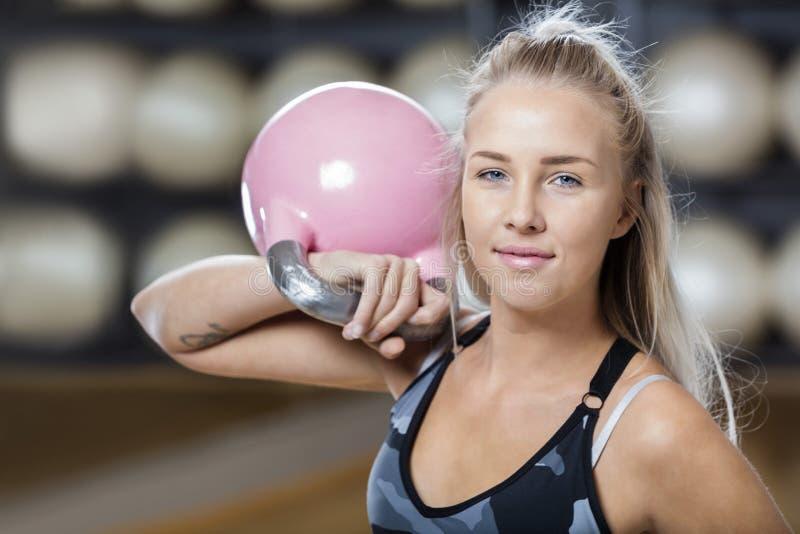 Zekere Jonge Vrouw die Kettlebell in Gymnastiek opheffen stock foto's