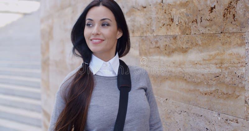 Zekere jonge vrouw die tegen muur leunen royalty-vrije stock afbeelding