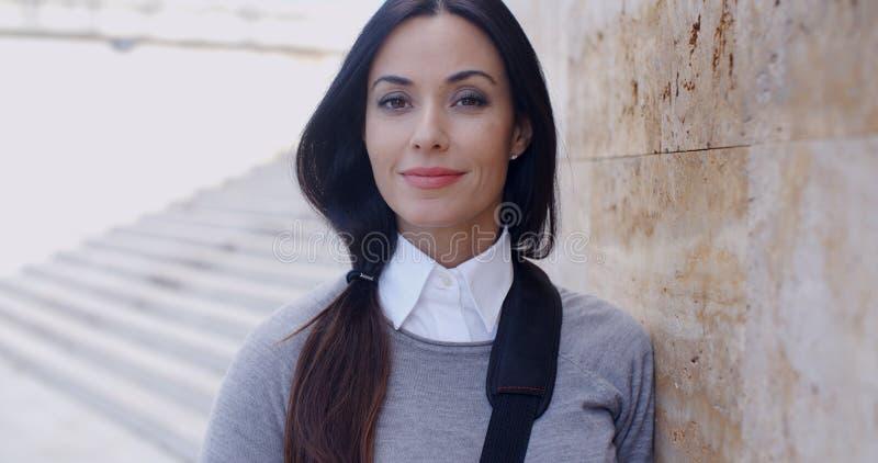 Zekere jonge vrouw die tegen muur leunen stock fotografie