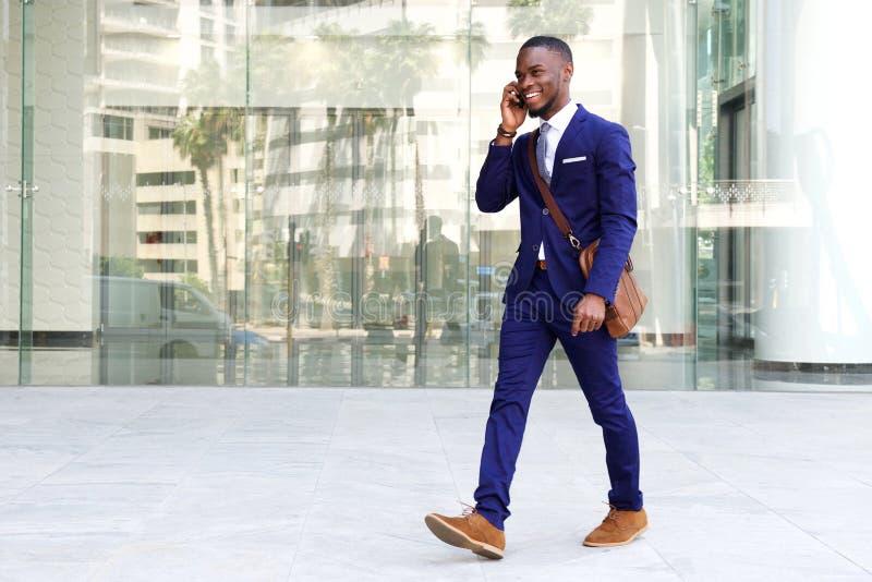 Zekere jonge zakenman die celtelefoon in stad met behulp van royalty-vrije stock foto