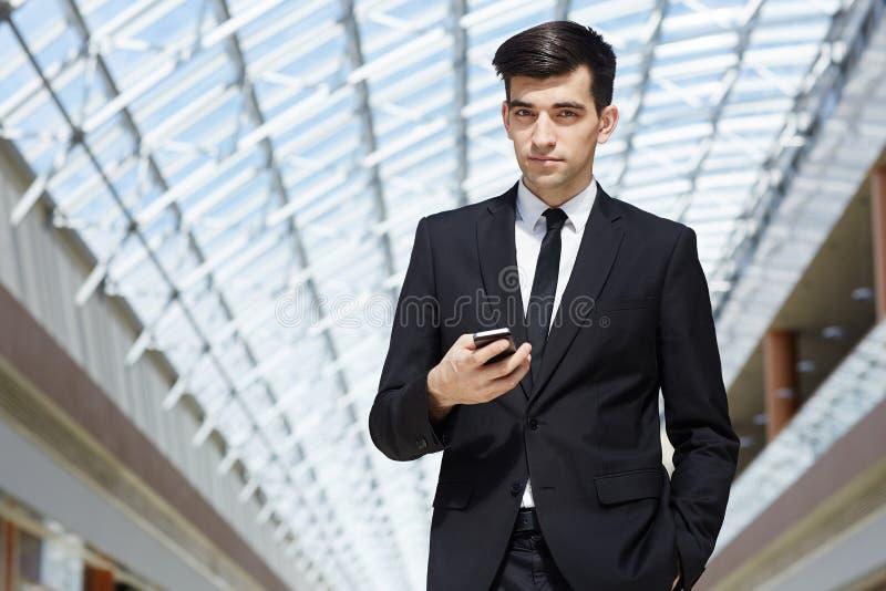 Zekere Jonge Zakenman Using Smartphone in Glaszaal royalty-vrije stock afbeeldingen