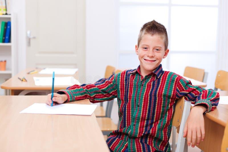Zekere jongenszitting alleen in klaslokaal stock foto