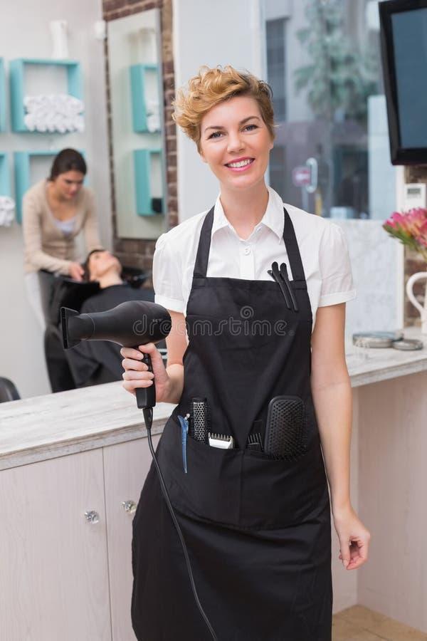 Zekere kapper die bij camera glimlachen stock fotografie