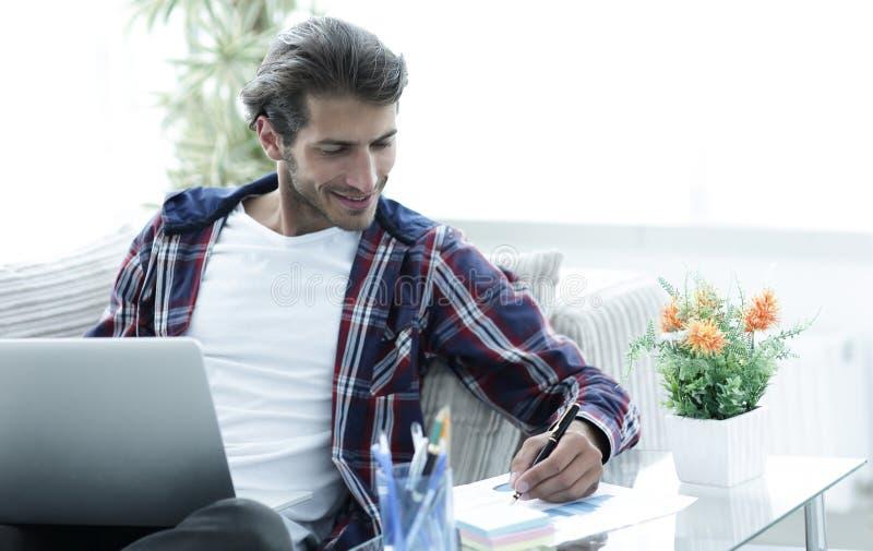 Zekere kerel die met laptop thuis werken stock fotografie
