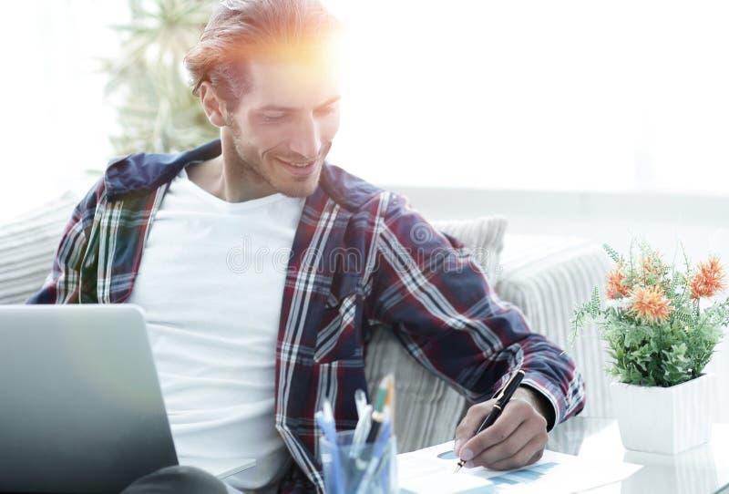 Zekere kerel die met laptop thuis werken royalty-vrije stock afbeelding