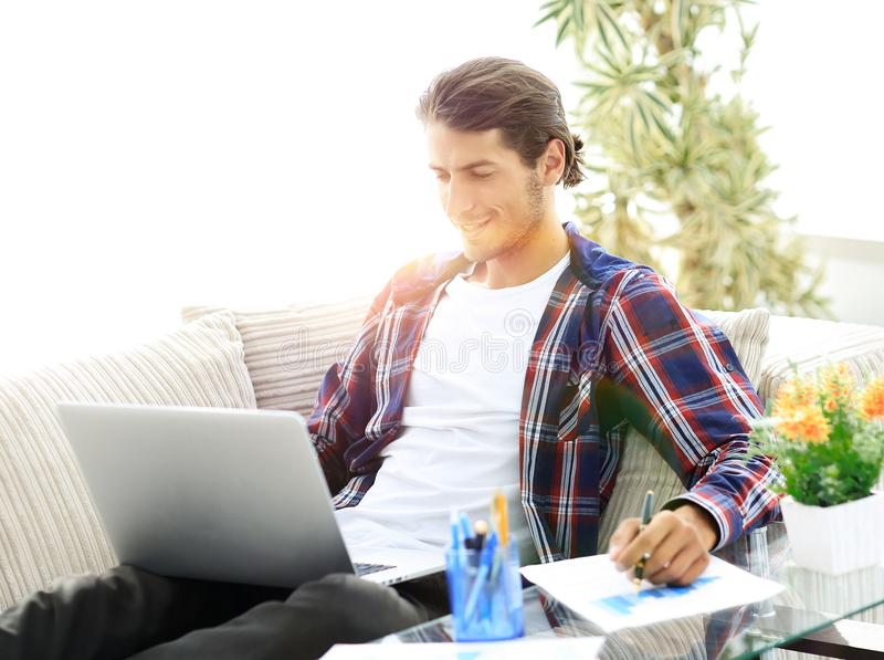 Zekere kerel die met laptop van huis werken concept freelanc royalty-vrije stock fotografie