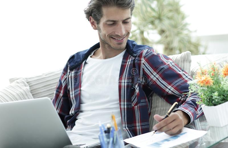 Zekere kerel die met laptop van huis werken Concept het freelancing stock afbeeldingen