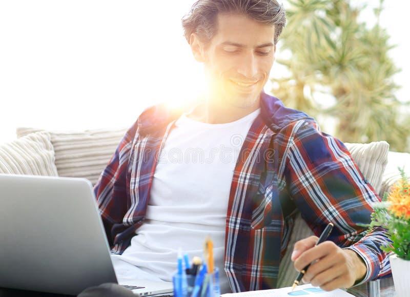 Zekere kerel die met laptop van huis werken Concept het freelancing royalty-vrije stock fotografie