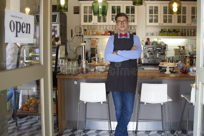 Zekere kleine bedrijfseigenaar jonge mens die zich in zijn koffie bevinden stock fotografie