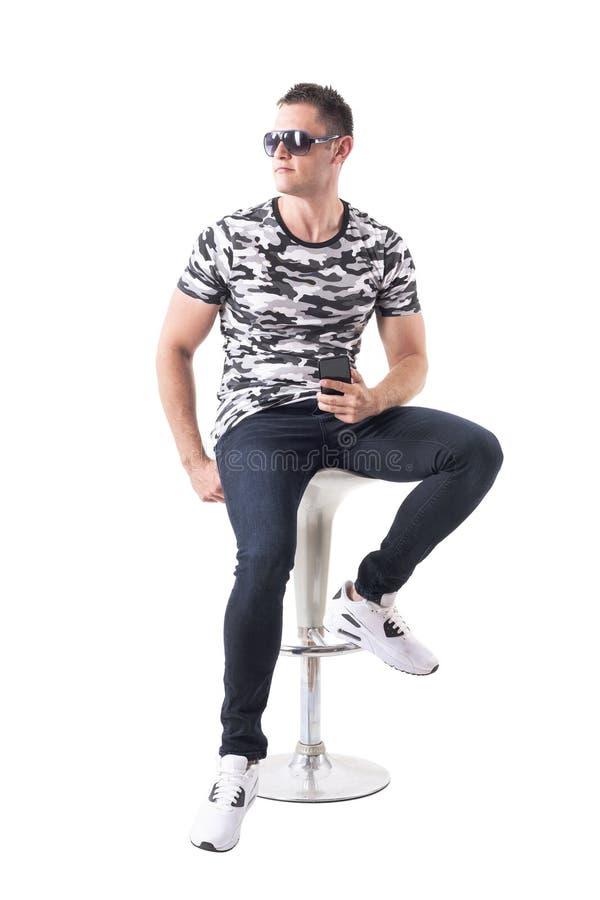 Zekere knappe mens die in camooverhemd met zonnebril op barkruk zitten die weg eruit zien stock fotografie