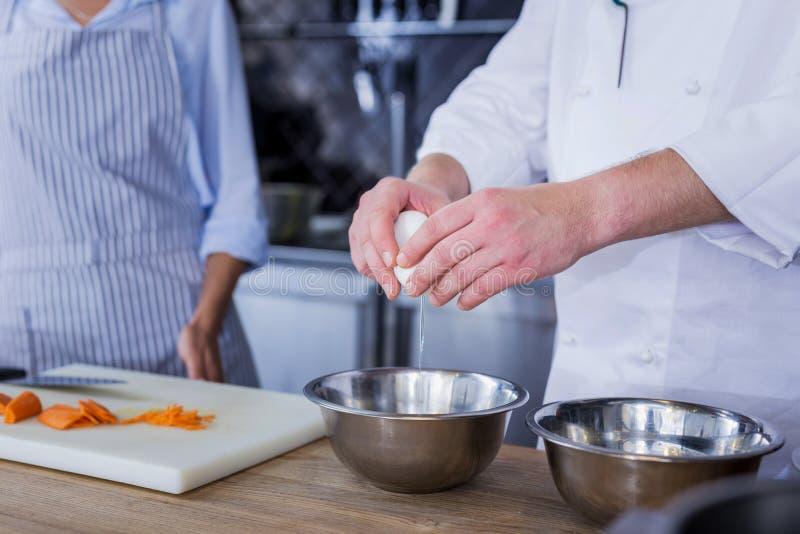 Zekere kok die nieuwe ingrediënten toevoegen aan een schotel stock afbeelding