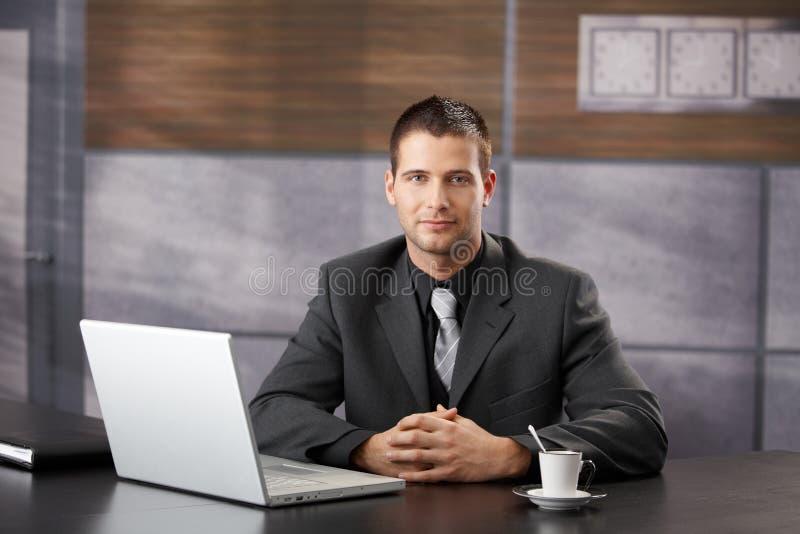 Zekere managerzitting in het buitensporige bureau glimlachen royalty-vrije stock afbeeldingen