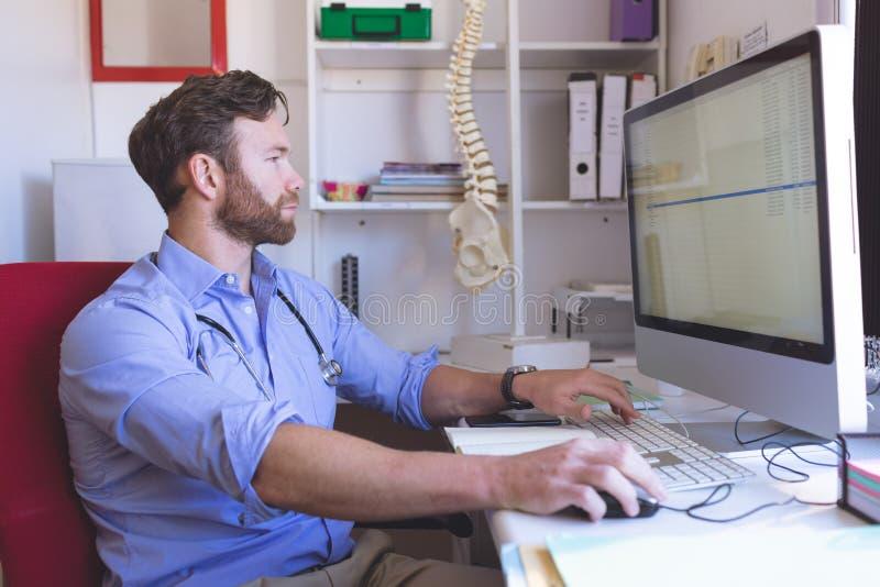 Zekere mannelijke arts die aan computer in kliniek werken stock afbeelding