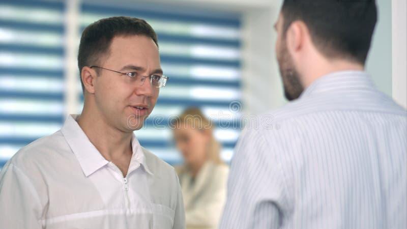 Zekere mannelijke arts die aan mannelijke patiënt spreken stock afbeeldingen