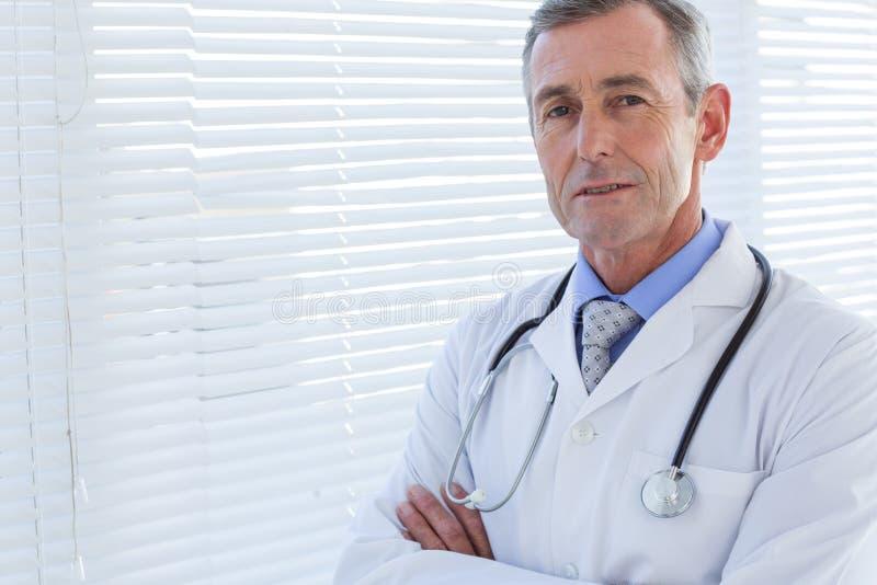 Zekere mannelijke arts die camera met gekruiste wapens bekijken stock afbeeldingen