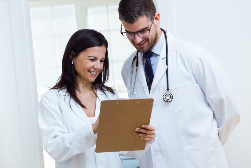 Zekere mannelijke arts en zijn verpleegster die in het bureau werken stock afbeeldingen