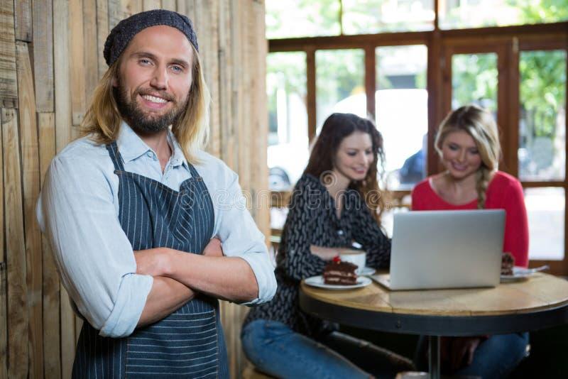 Zekere mannelijke barista met vrouwelijke klanten op achtergrond bij koffie stock afbeeldingen