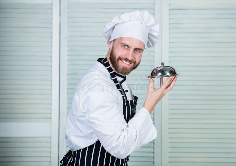 zekere mens in schort en hoedengreepdienblad kok in eenvormig restaurant, de gebaarde mens houdt van etend voedsel chef-kok klaar royalty-vrije stock fotografie
