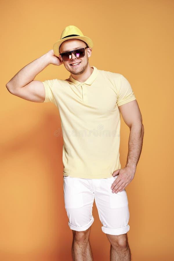 Zekere modieuze kerel in geel overhemd, zonnebril die, witte borrels, strohoed camera bekijken stock foto