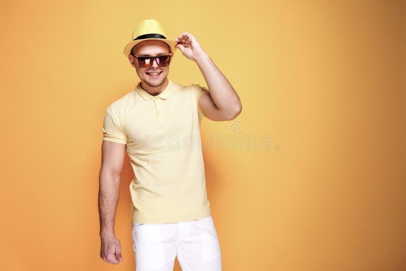 Zekere modieuze kerel in geel overhemd, zonnebril die, witte borrels, strohoed camera bekijken royalty-vrije stock afbeelding