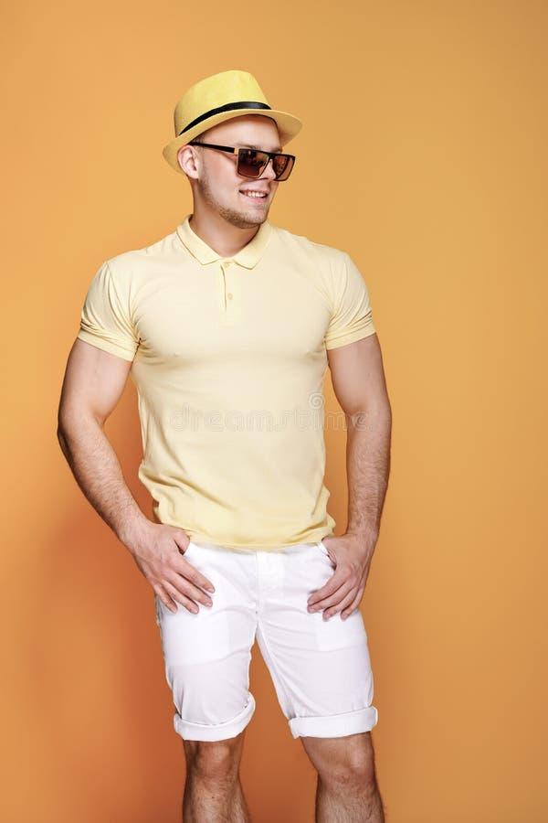 Zekere modieuze kerel in geel overhemd, zonnebril die, witte borrels, strohoed kant vanaf camera kijken stock fotografie