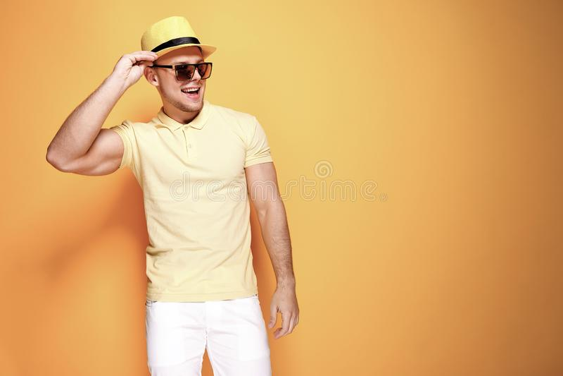 Zekere modieuze kerel in geel overhemd, zonnebril die, witte borrels, strohoed kant vanaf camera kijken royalty-vrije stock foto