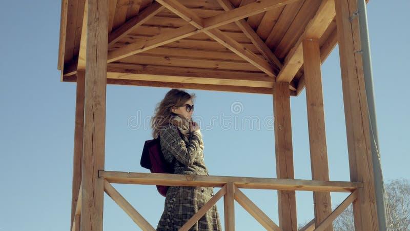 Zekere mooie bedrijfsvrouw die in de houten de reddingstoren van A op het strand tijdens de afwezigheid van sesosis lopen royalty-vrije stock foto's