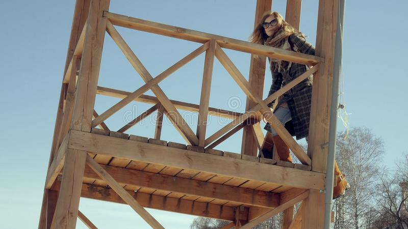 Zekere mooie bedrijfsvrouw die in de houten de reddingstoren van A op het strand tijdens de afwezigheid van sesosis lopen royalty-vrije stock afbeelding
