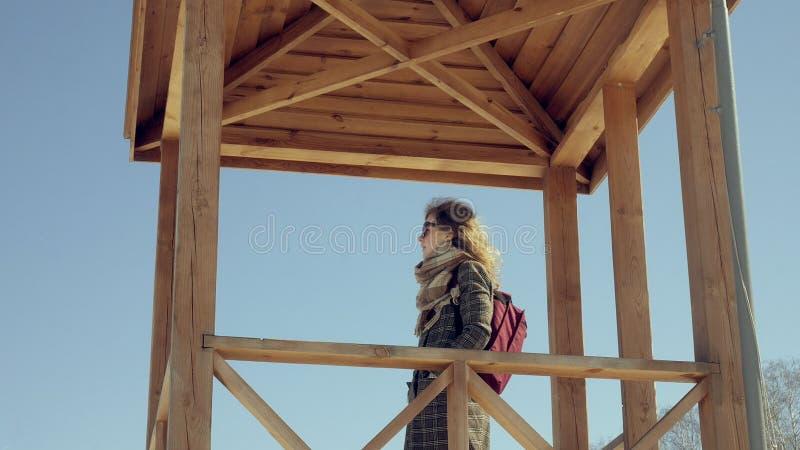 Zekere mooie bedrijfsvrouw die in de houten de reddingstoren van A op het strand tijdens de afwezigheid van sesosis lopen royalty-vrije stock fotografie